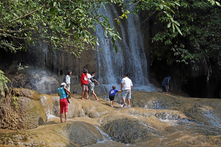 PATTAYA, THAILAND - DECEMBER 29, 2013: Tourists swim in the streams of Sai Yok Waterfall