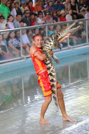 PATTAYA, THAILAND-MARCH 20, 2019: Cheerful tamer in the arena holding a crocodile 新聞圖片