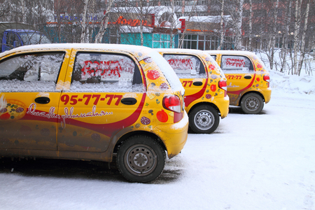 SURGUT, RUSSIA-MARCH 15, 2012: Three yellow snow-covered pizza delivery vehicles