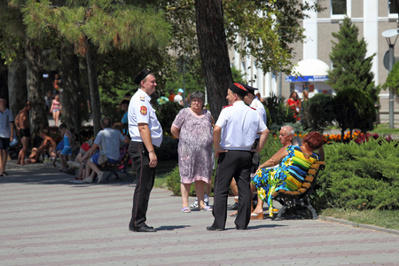 GELENDZHIK, RUSSIA-AUGUST 08, 2015: a Joint Cossack patrol and police officers talk on the street with vacationing tourists on a Sunny summer day at the black sea resort