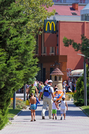 GELENDZHIK, RUSSIA-AUGUST 08, 2015: a Family goes to the McDonalds cafe on the resort embankment 에디토리얼