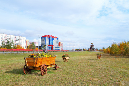 Novy Urengoy, RUSSIA-SEPTEMBER 08, 2012: Horse cart as a flower bed with flowers in the field on the background of the hotel and business center Builder and the temple of Seraphim Sorovsky