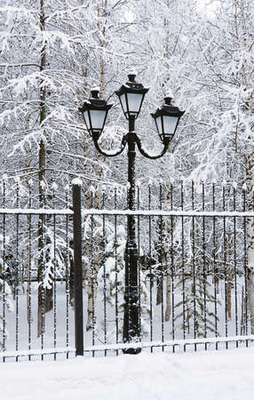 Fence and street lamp after a snowfall in Siberia