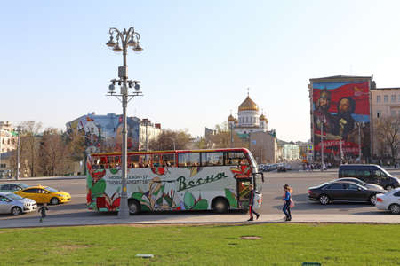 MOSCOW, RUSSIA-APRIL 30, 2017: Tourist bus on the background of the Cathedral of Christ the Savior and graffiti depicting the heroes of Russian history Minin and Pozharsky, Mikhail Kutuzov Editorial