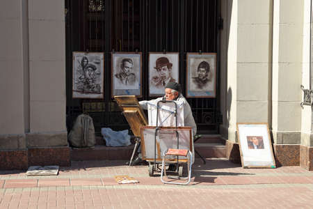 MOSCOW, RUSSIA-APRIL 30, 2017: An elderly artist paints portraits of famous politicians and musicians for tourists on Arbat Street in the Russian capital