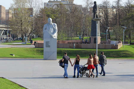 Moscow, RUSSIA-APRIL 29, 2017: Families walk near the monument to the Soviet designer of rocket and space technology Vladimir Chelomey on the Avenue of Cosmonauts Editorial