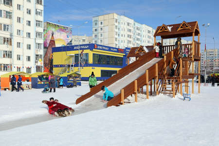 Nadym, RUSSIA-MARCH 14, 2021: Children have fun and ride down the slide on a sunny frosty day during the Maslenitsa holiday Editorial