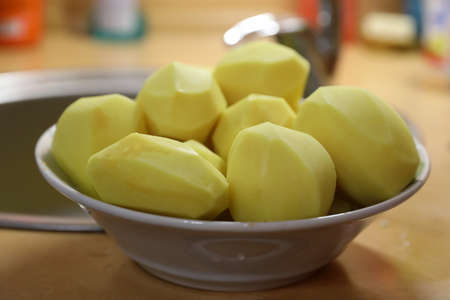 Peeled potato tubers in a plate in the home kitchen