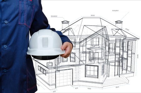 Construction hard hat in hand. House model Stock Photo