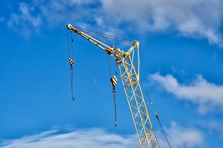 Yellow Industrial Cranes Working on Construction Site Against Blue Sky Stock Photo