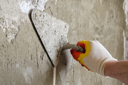 plasterer concrete worker at wall of house construction Stock Photo - 57191546