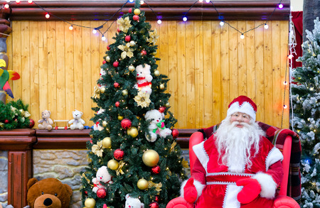 Good old Santa Claus having a rest in his house next to the fireplace and Christmas tree. Stock Photo