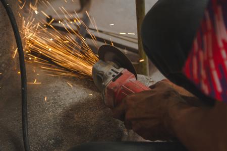 Craftsman sawing metal sparkles all around workshop