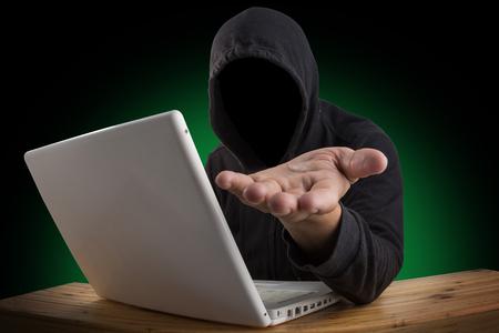 hacker hacking computer network with laptop, Dark face hacker Imagens
