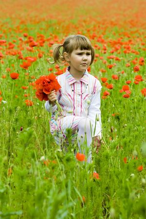 Girl on meadow with a red poppies
