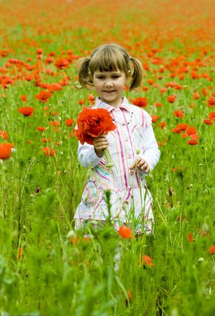 Girl on meadow with a red poppies  photo