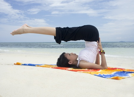 young woman doing yoga exercise at the beach