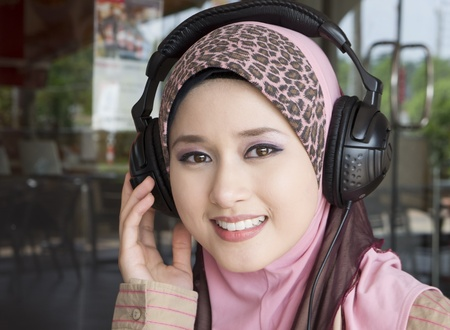 only one woman: young muslim girl smile with headphones  Stock Photo