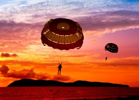 """spadochron: Sylwecie para żeglarzy na zachód sÅ'oÅ""""ca Zdjęcie Seryjne"""