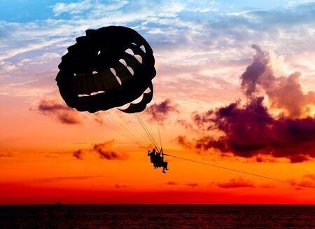 gliding:  Silhouette of a para-sailor at sunset