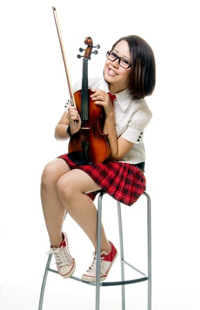 Young and pretty teenager school girl poses with violin, isolated background photo