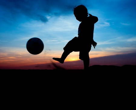 silhouette of boy kick the ball photo