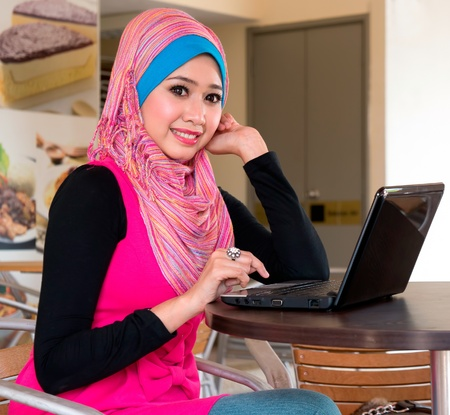 pretty muslim girl with laptop at cafe photo