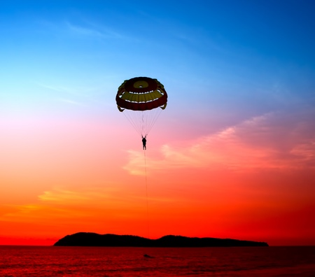 thrill: Silhouette of a parasailor at sunset