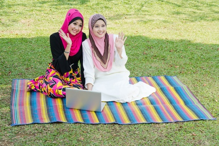 two young muslim woman say hi to their friends at park photo