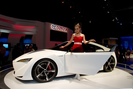 KUALA LUMPUR - DEC 03: An Asian Model pose with hybrid car from toyota, a concept car at International Motor Show 2010  on DECEMBER 3, 2010 in Kuala Lumpur, Malaysia