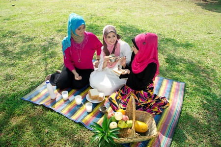 young muslim woman in hijab while relaxing and eating with friends in the park   photo