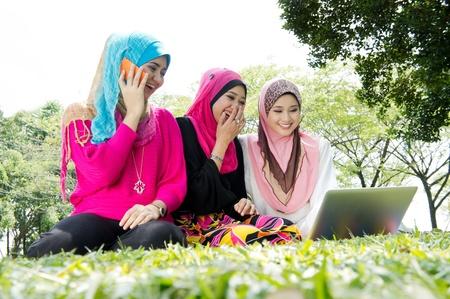 femmes muslim: jeune femme musulmane heureuse utilisant un ordinateur portable avec des amis