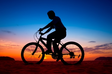 silhouette of a cyclist at sunset photo