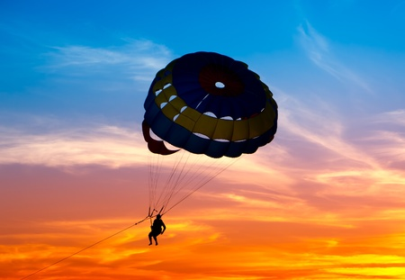 Silhouette of a parasailor at sunset  photo