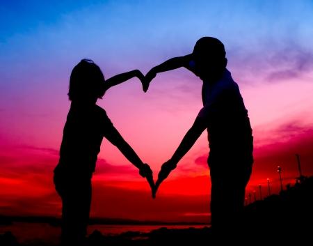 cuore in mano: coppia silhouette giovane rendendo forma di cuore con le braccia sulla spiaggia al tramonto