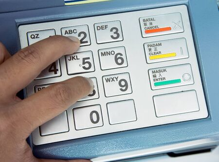 automatic teller machine bank: Finger pressing password number on ATM machine