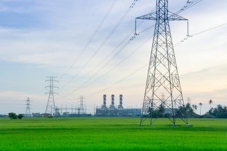 torres de alta tension: Torres de electricidad con planta de energía en el horizonte