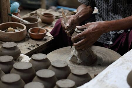 potter: Potter molding clay pot at very low light place. Stock Photo