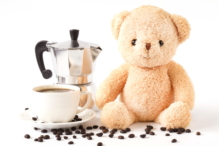 Bear doll sitting with black coffee cup and coffee maker isolated