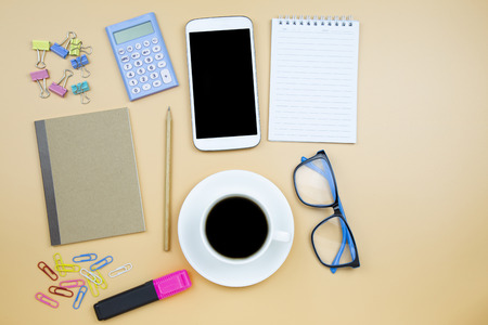 Notebook brown cover mobile phone calculator and black coffee white cup blue glasses on orange background pastel style with copyspace flatlay Stock fotó