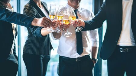 Group of business people toasting champagne glasses for the celebration of successful business.