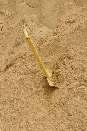 A shovel digging into pile of building sand photo