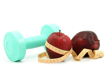 Fresh red apple with measuring tape and dumbbell