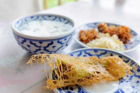rice in ice water, thai appetizer, with side dishes food which are fried pork, fried chili and vegetable  Stock Photo
