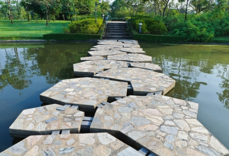 across: Stone path across the pond in the park Stock Photo