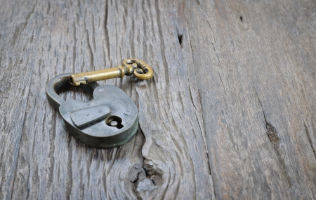 Old padlock and key on a wooden table background photo