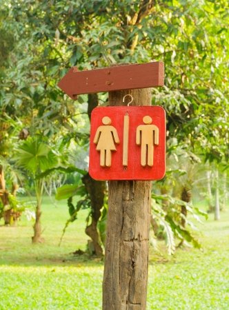Wooden Sign pointing direction go to toilet photo