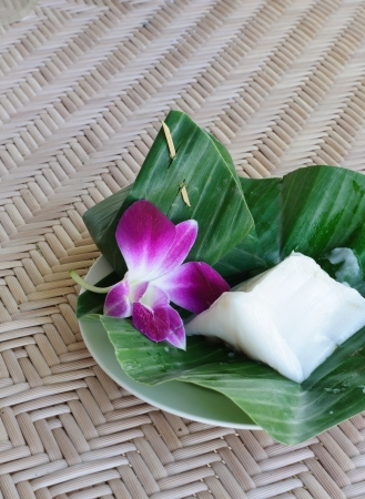 Thai dessert. Coconut milk and Steamed rice dough with sweet coconut stuffing wrapped in banana leaves