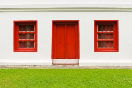 The old door and windows red on white wall and green grass filed Stock Photo - 17618326