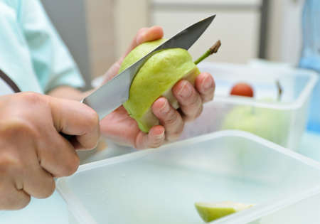 A Woman hands peeling guava with a knife .